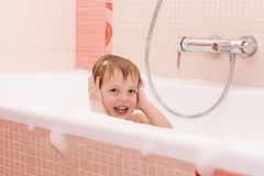 Funny little baby boy playing with foam in a bath tub.  royalty free stock image