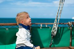 Funny little baby captain on board of sailing yacht Royalty Free Stock Image