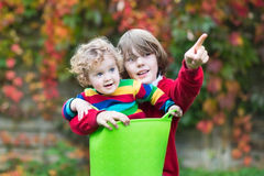 Funny little baby girl and her brother in the garden Royalty Free Stock Images