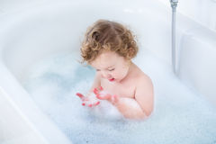 Funny little baby girl playing with foam in bath tub Royalty Free Stock Photos