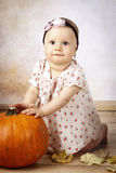 Funny little baby girl with pumpkin Stock Photography