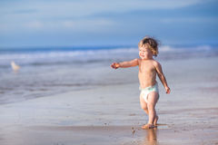 Funny little baby girl running on tropical beach Stock Image