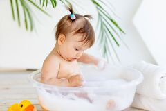 Funny little baby girl washes in a basin with foam and water in a bright room at home