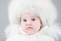 Funny little baby girl wearing a huge fur hat Royalty Free Stock Photo