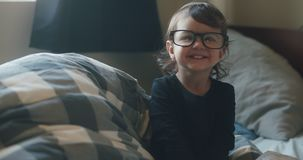 Funny little baby girl wearing parents glasses on bed.