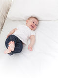 Funny little baby girl on white bed Royalty Free Stock Photos
