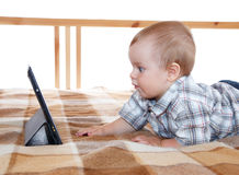 Funny little baby looking at his tablet pc Stock Photos
