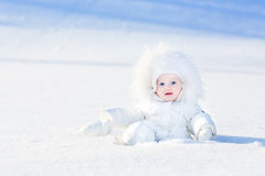 Funny little baby playing in snow on sunny day Stock Photos