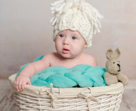 Funny little baby sitting in basket Stock Photo