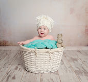 Funny little baby sitting in basket Royalty Free Stock Image
