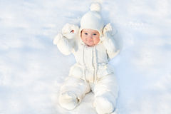 Funny little baby sitting in fresh snow. Wearing a white jacket and hat Royalty Free Stock Photo