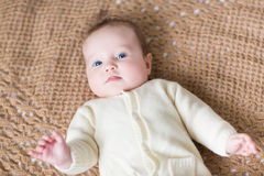 Funny little baby in warm sweater on knitted blanket Royalty Free Stock Photo