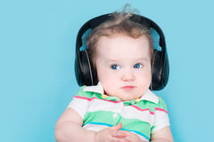 Funny little baby wearing huge black earphones Royalty Free Stock Image