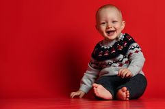 Funny little baby wearing warm knitted Christmas sweater at studio on cold winter day. royalty free stock photography