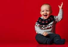 Funny little baby wearing warm knitted Christmas sweater at studio on cold winter day. royalty free stock image