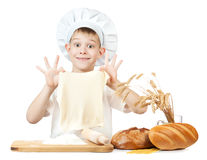 Funny little baker is kneading dough Stock Photos
