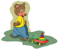 Funny little bear pulling a toy car Royalty Free Stock Photography
