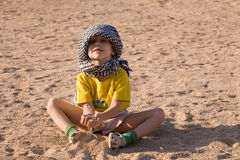 Funny little bedouin. Little girl sitting on sand in t-shirt and bedouin kerchief royalty free stock photos