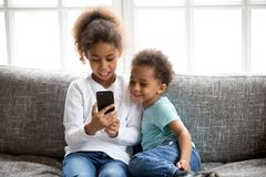Funny little black kids have fun playing on smartphone royalty free stock photos