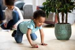Funny little black toddler play with toy car royalty free stock image