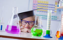 Funny little blonde looks on flasks with reagents Royalty Free Stock Image