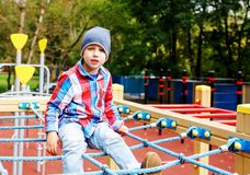 Funny little boy clime in the rope web on playground. Cute boy play and climb outdoors on sunny summer day.  royalty free stock photography