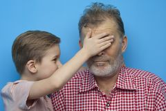 Funny little boy closes his eyes to grandfather stock image