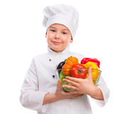 Funny little boy-cook holding bowl with vegetables in hands Royalty Free Stock Images