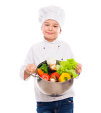 Funny little boy-cook holding bowl with vegetables in hands Royalty Free Stock Photos