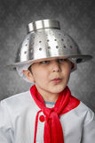A funny little boy cook in uniform over vintage  background. Cooking Royalty Free Stock Image