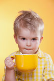 Funny Little Boy Drinking From Big Yellow Cup Royalty Free Stock Photo