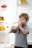 Funny little boy drinking milk near open fridge Royalty Free Stock Photos