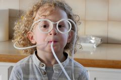 Funny little boy drinking with a straw. A funny little boy drinking with a straw stock image