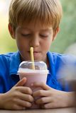 Funny little boy drinks milkshake Royalty Free Stock Photography
