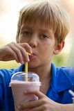 Funny little boy drinks milkshake Stock Photo