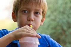 Funny little boy drinks milkshake Royalty Free Stock Photo