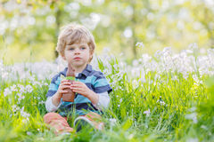 Funny little boy eating chocolate bunny  at Easter holiday Stock Photography