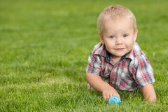 Funny little boy on the green grass Royalty Free Stock Photos