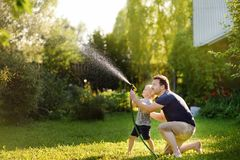 Funny little boy with his father playing with garden hose in sunny backyard. Preschooler child having fun with spray of water. Summer outdoors activity for royalty free stock photos