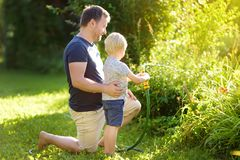 Funny little boy with his father playing with garden hose in sunny backyard. Preschooler child having fun with spray of water royalty free stock photography