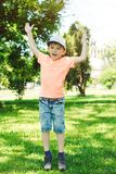 Funny little boy jumping in summer park. Happy child having fun outdoors. Happy and healthy childhood. Playful child boy on summer royalty free stock photo