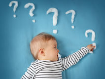 Funny little boy with lots of question marks Royalty Free Stock Photo