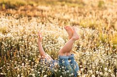 Funny little boy lying in a chamomile field. Lifting legs up royalty free stock images