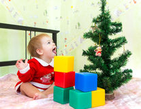 Funny little boy with open mouth looks at new year fir. Near bricks Stock Photography