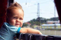 Funny little boy picking out from train window. Outside, while it moving. fluttering hair Royalty Free Stock Image