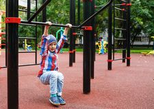 Funny little boy on playground. Cute boy play and climb outdoors on sunny summer day. Funny little boy on playground. Cute boy play and climb outdoors on sunny royalty free stock photo