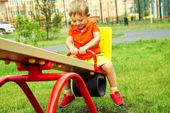 Funny little boy on playground. playing child on swing. Funny little boy on playground. playing child on a swing stock photography