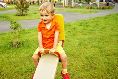 Funny little boy on playground. playing child on swing. Funny little boy on playground. playing child on a swing royalty free stock photos