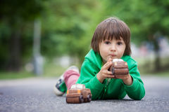 Funny little boy playing with car of chocolate, outdoor Royalty Free Stock Photos