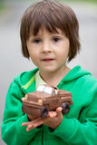 Funny little boy playing with car of chocolate, outdoor Royalty Free Stock Photography